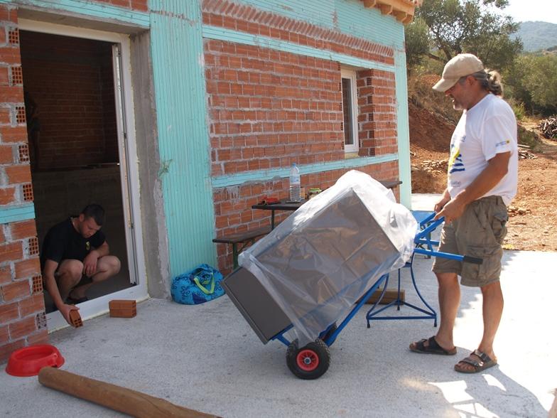 Der schwere Holzofen mit Backrohr wird in das Haus geschafft (einen Sackkarren dazu haben wir uns erworben, damit können wir zukünftig die schweren großen Steine leichter transportieren)