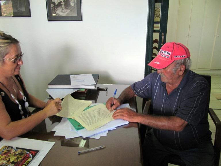 Kostas unterzeichnet den Grundstücks Kauf- & Übergabe Vertrag