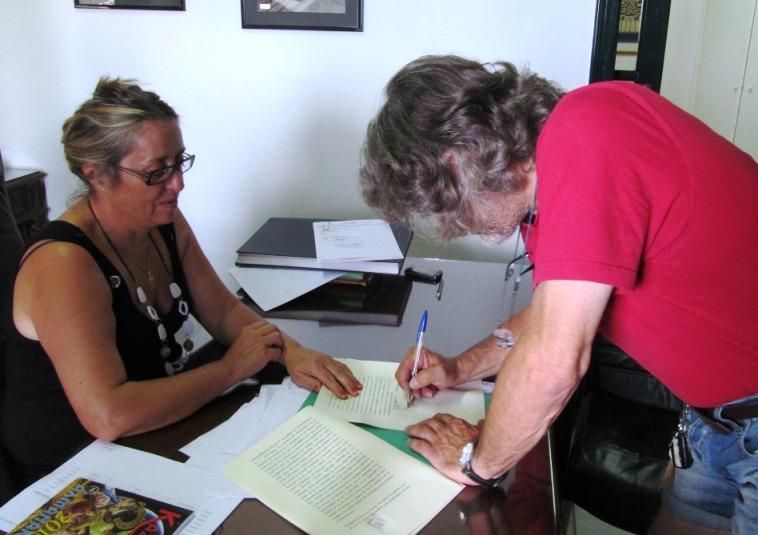 Manfred unterzeichnet den Grundstücks Kauf- & Übergabe Vertrag