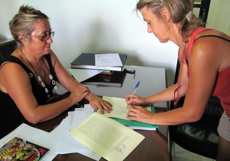 Silke unterzeichnet den Grundstücks Kauf- & Übergabe Vertrag