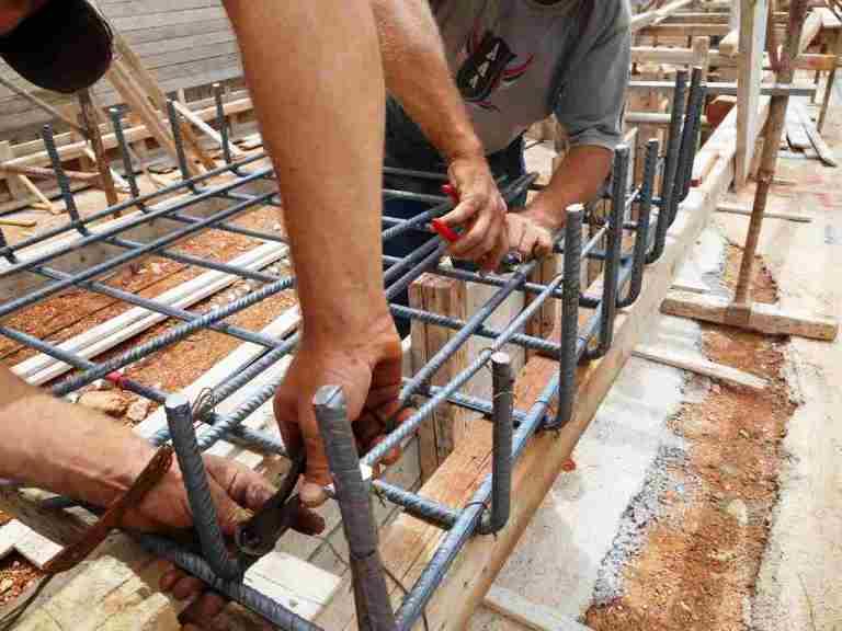Fleissige Hände binden fachmännisch Eisenstäbe für die Armierungskörbe der Fundamente