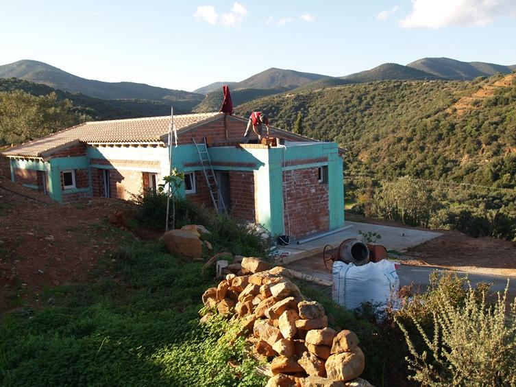 während Steine für den Holzofen Unterbau gesammelt werden wird der Rand zur Entwässerung am Flachdach gemauert