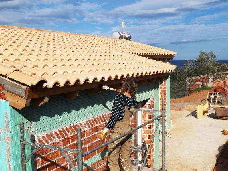 Silke streicht den Dachvorsprung mit Holzschutz Lasur