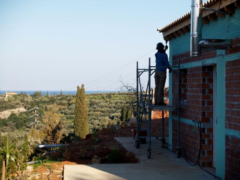 Silke streicht das Holz am Dachvorsprung